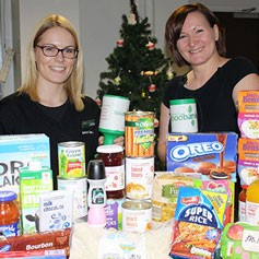 Two Partners holding up collection tins for the Trussell Trust FoodBank and in front of a food collection